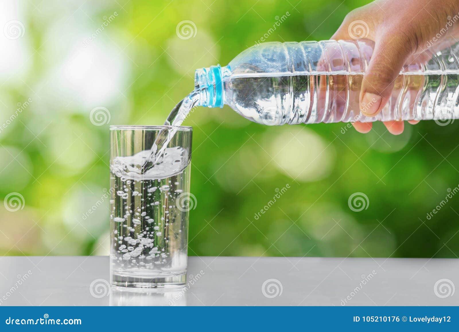 вручите лить питьевую воду в стеклянную бутылку формы на таблице с