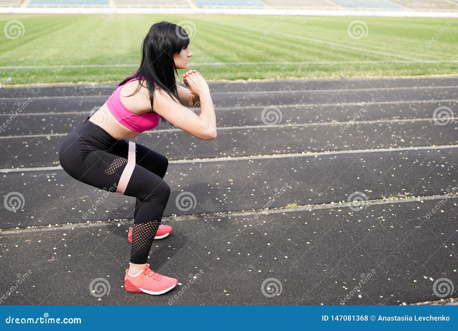 Всегда в хорошей форме Современная молодая женщина в одежде спорта скача пока работающ outdoors предпосылка фитнеса с местом для