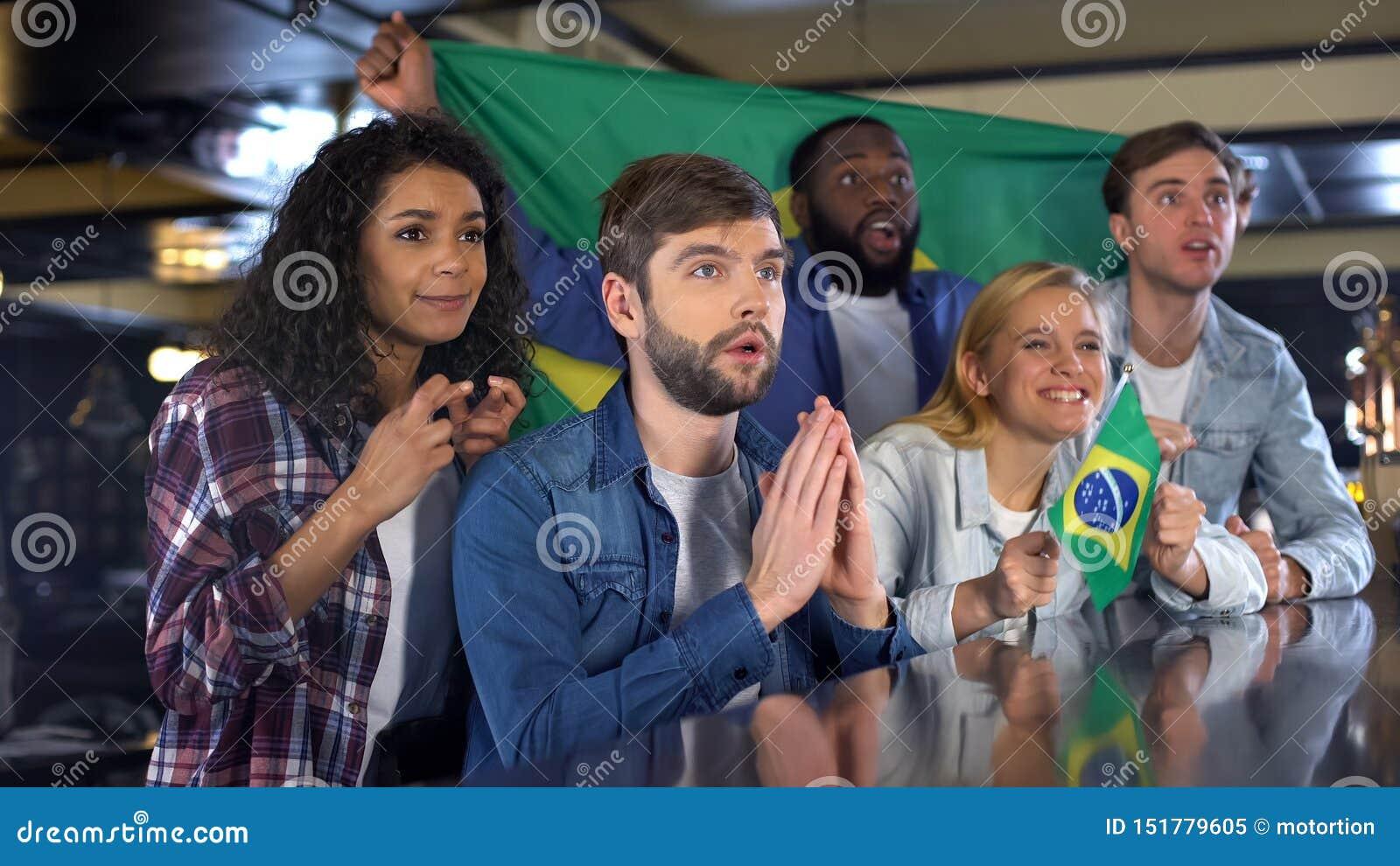 Встревоженные футбольные болельщики с бразильскими флагами поддерживая национальную команду в игре
