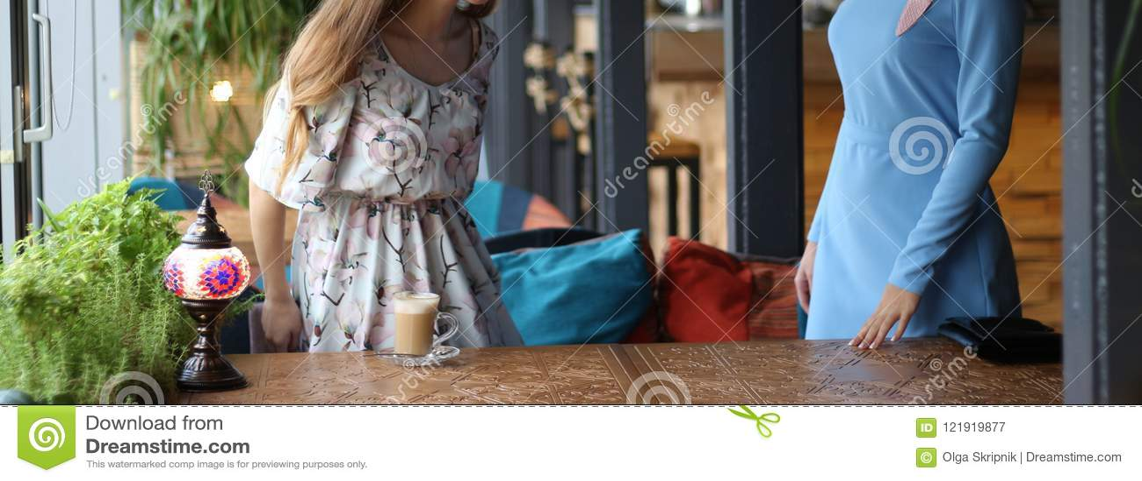 встречать 2 женщин в кафе для кофе , который стоят до приветствовать второе голубое платье, платье в цветке, на высекаенной табли