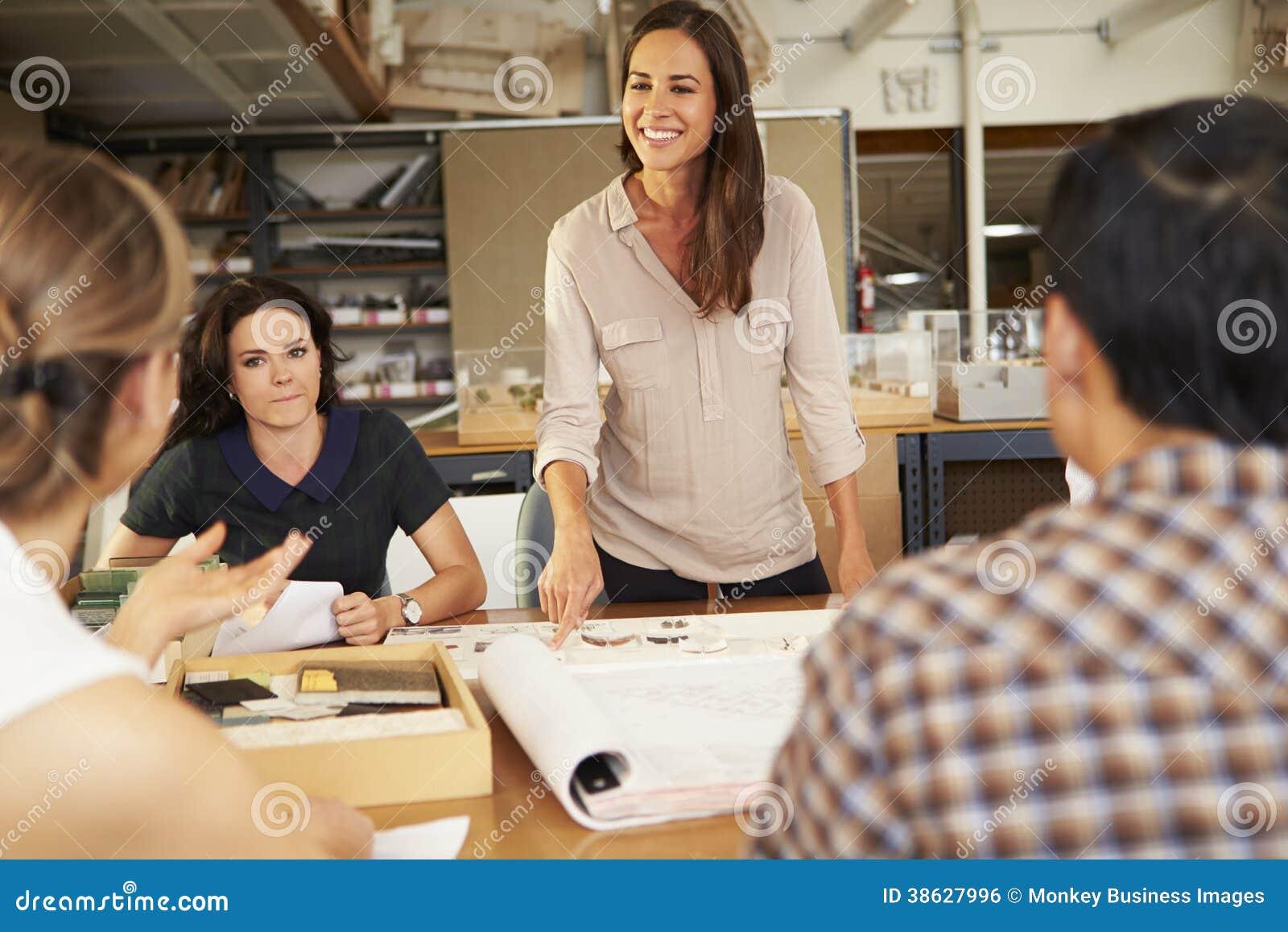 Встреча женского босса ведущая архитекторов сидя на таблице