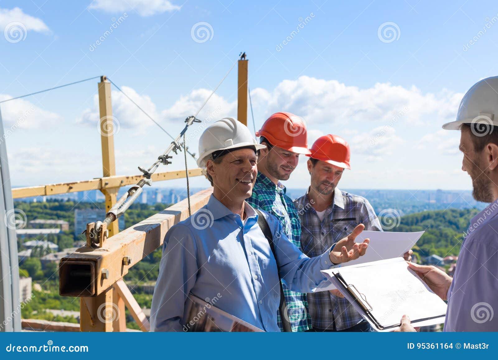 Встреча команды построителей при на строительная площадка обсуждая план проекта с подрядчиком архитектора