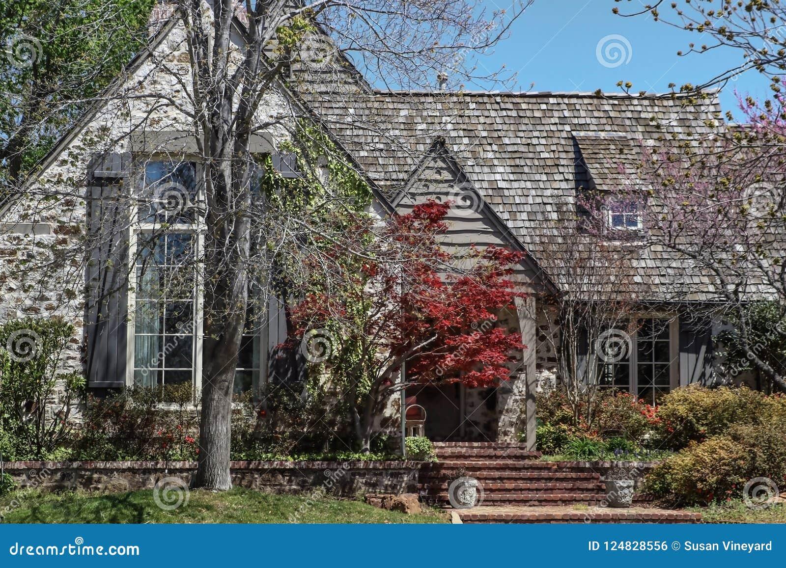 Вход к древесине постриг дом с японским кленом и деревянными штарками и лозами растя на стене в предыдущей весне