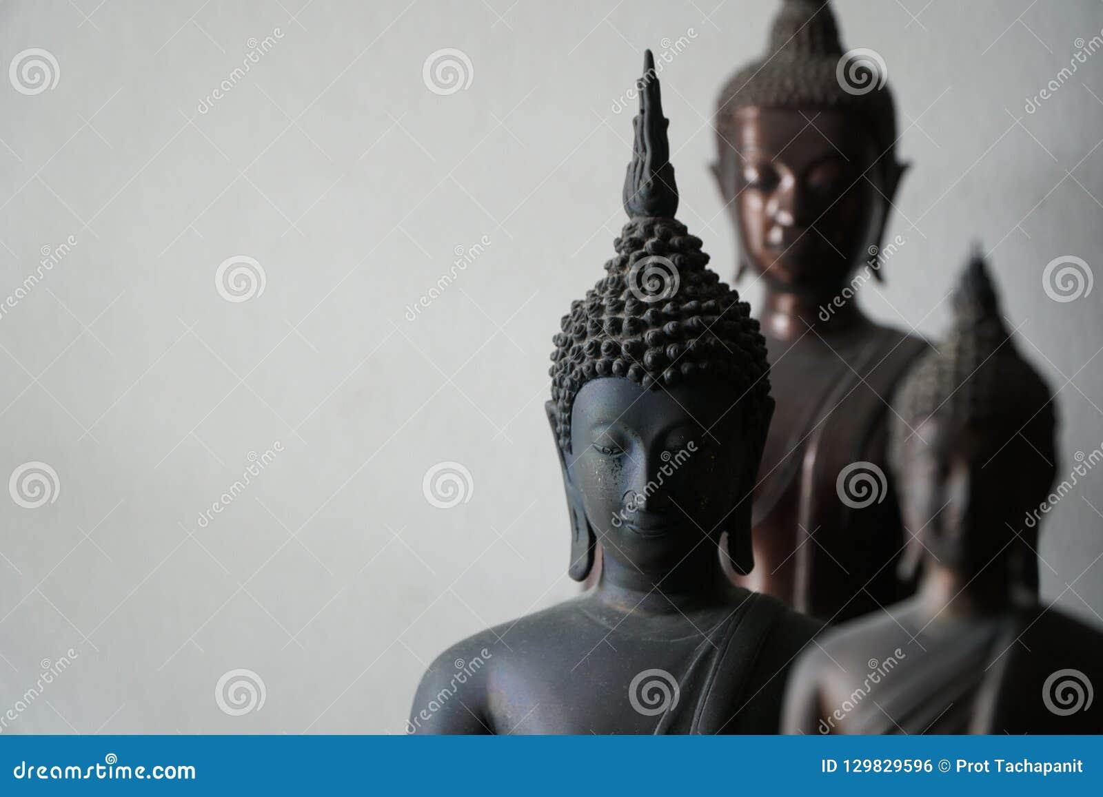 Выберите фокус винтажной черной старой статуи buddhas в середине другой статуи buddhas