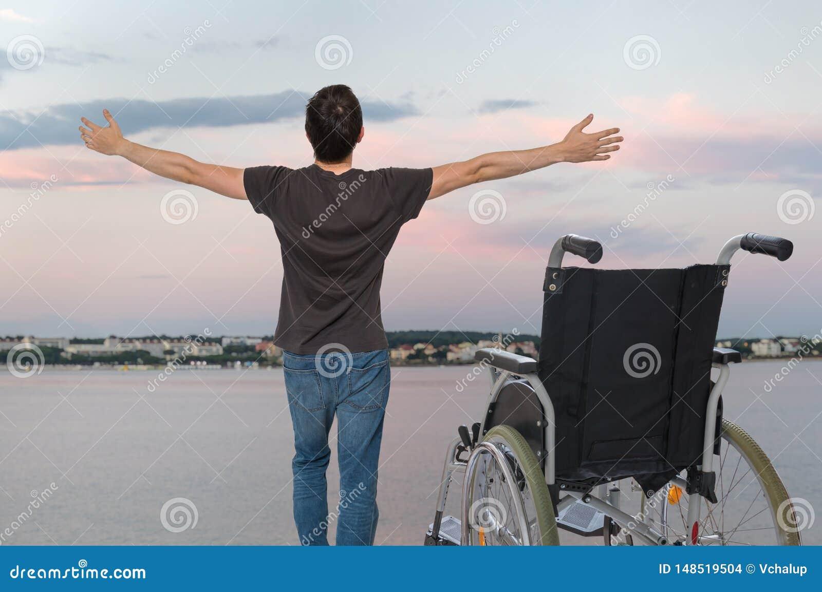 Выведенный из строя с ограниченными возможностями человек здоров снова Он счастлив и стоящ около его кресло-коляскы