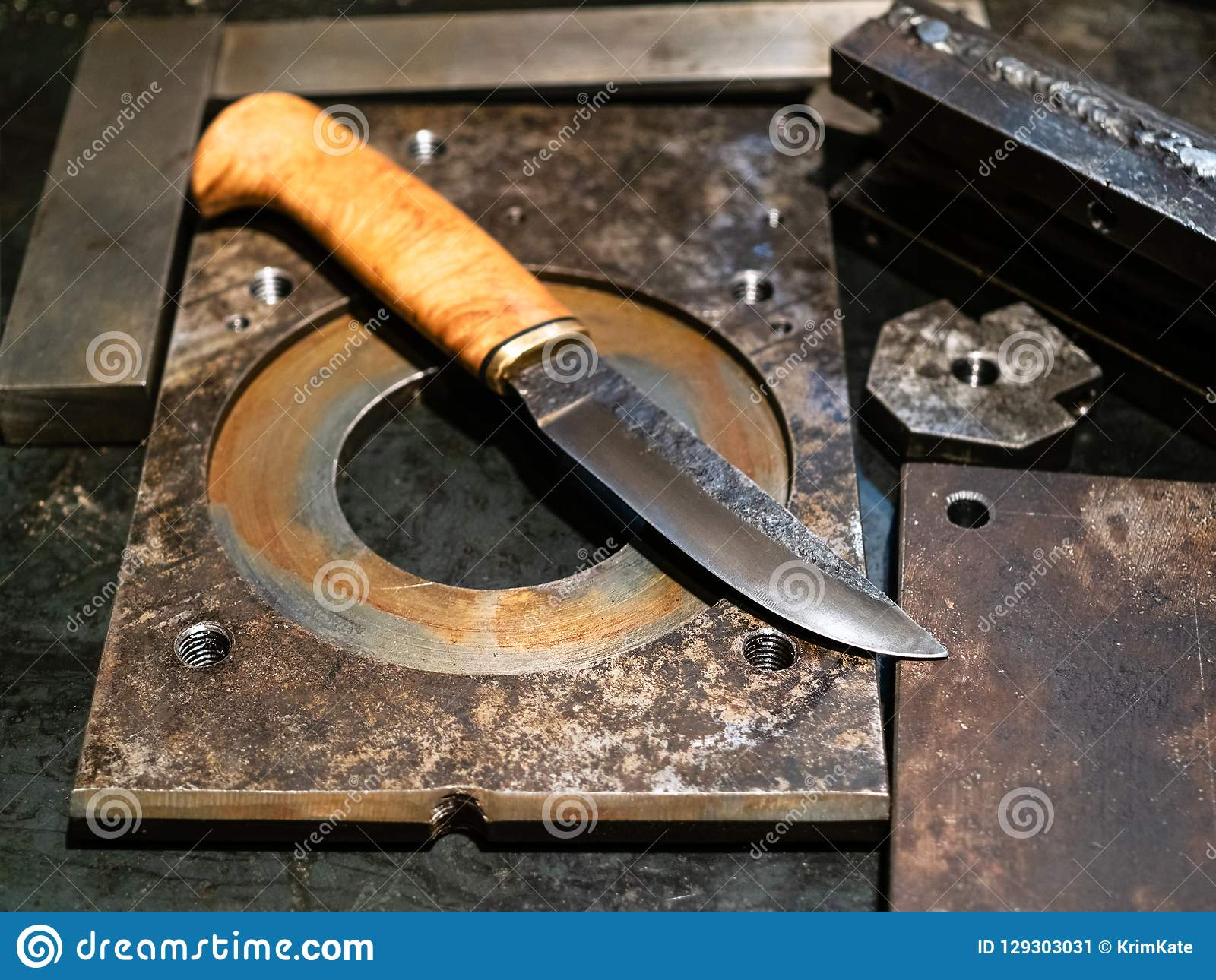 выкованный нож на верстаке металла