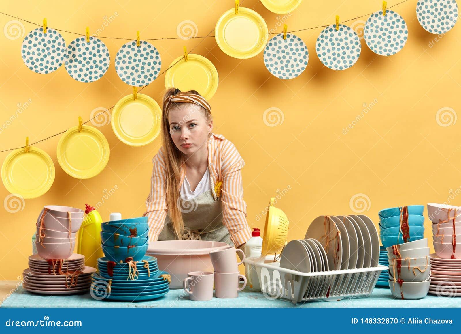 Вымотанное белокурое womna полагаясь на кухонном столе и смотря камеру