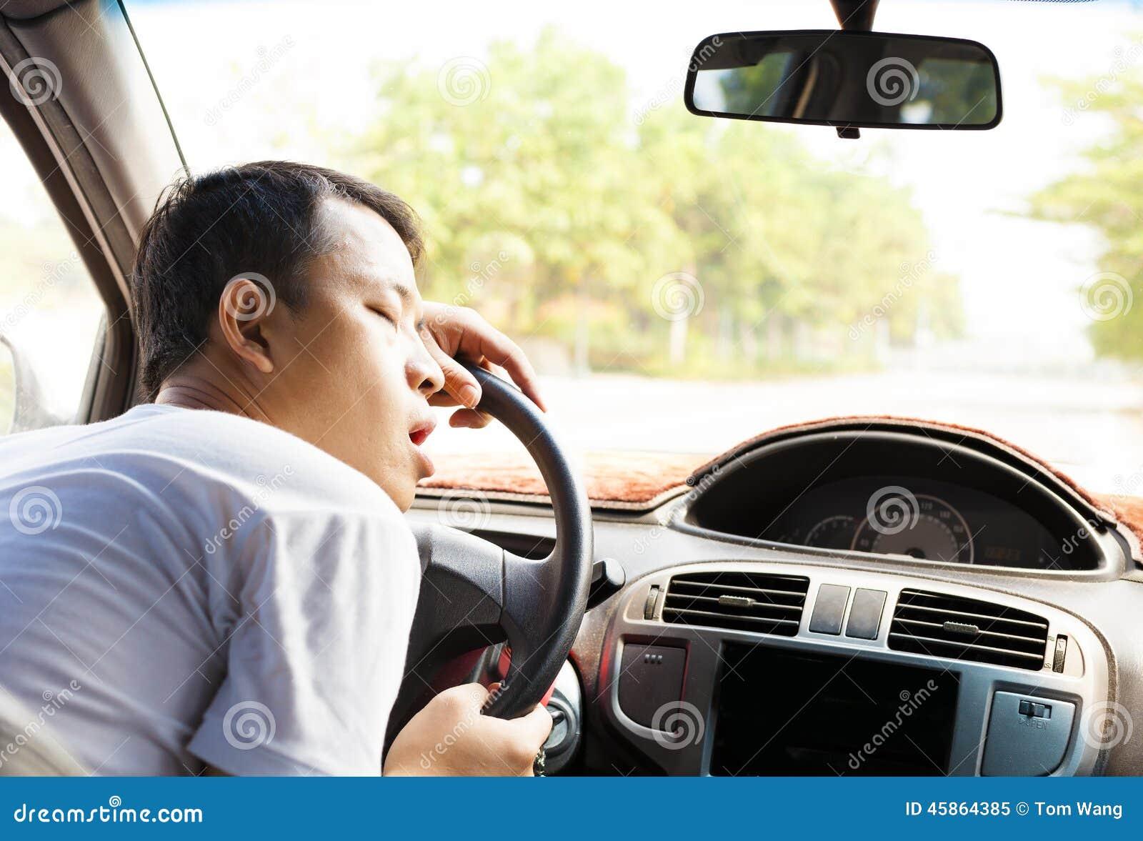 Вымотанный водитель отдыхая на рулевом колесе