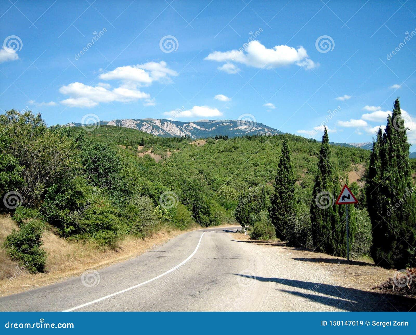 Вымощенная дорога с острыми поворотами в живописных предгорьях в южном на ясный день