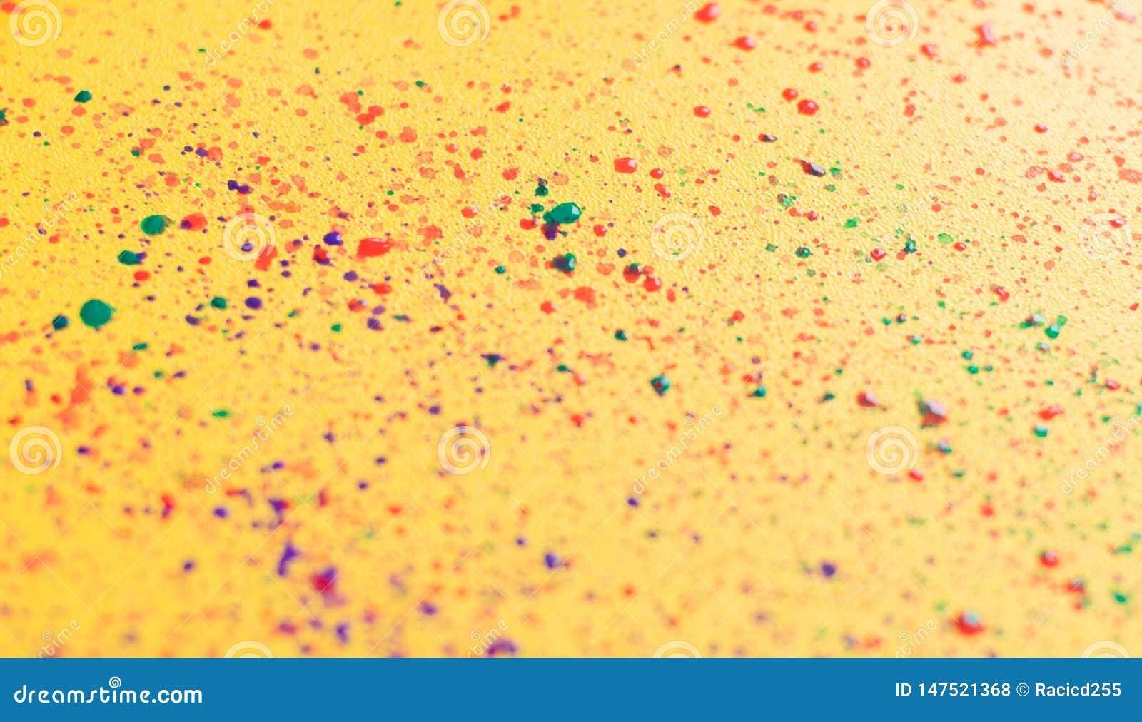 Выплеск красочного порошка над желтой затрапезной шикарной предпосылкой