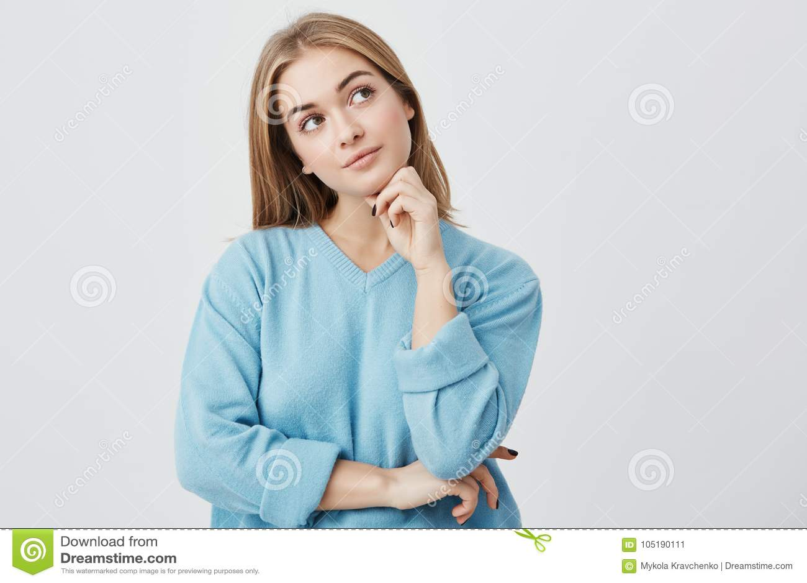 Выражения и эмоции стороны Заботливая молодая милая девушка в голубом свитере держа руку под ее головой, имеющ сомнительное