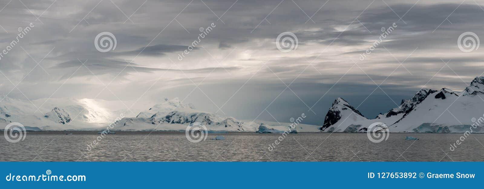 Высокопоставленные облака шторма над снег-покрытыми горами, проливом Gerlache, антартическим полуостровом