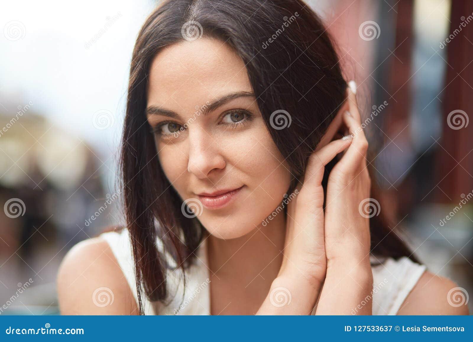 Выстрел в голову милой женщины с темными волосами, приятное возникновение, взгляды сразу на камере, представлениях внешних, выраж