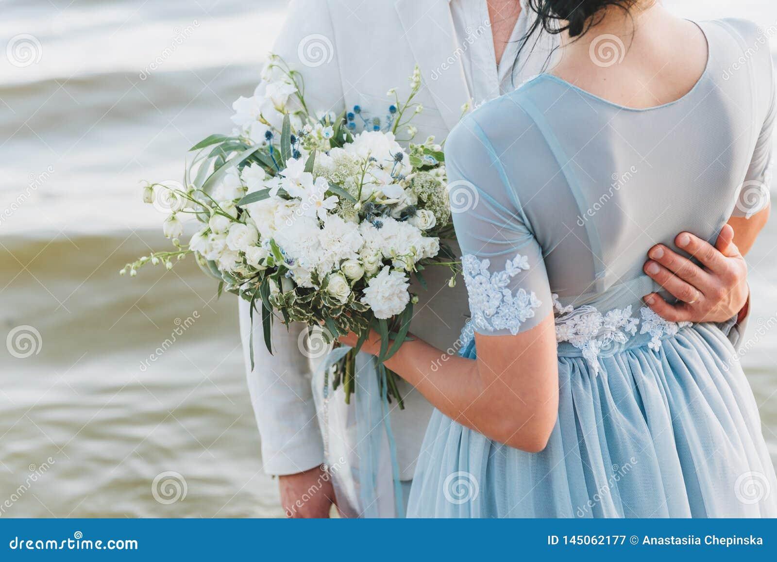 Выхольте иметь его руку на талии его невесты, стоя на пляже Невеста держит букет