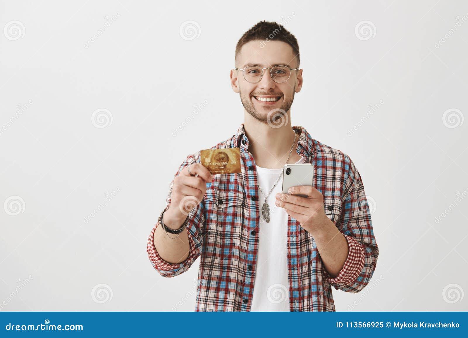 Вы должны получить эту карточку Привлекательный молодой сотрудник держа кредитную карточку и smartphone, усмехаясь обширно на