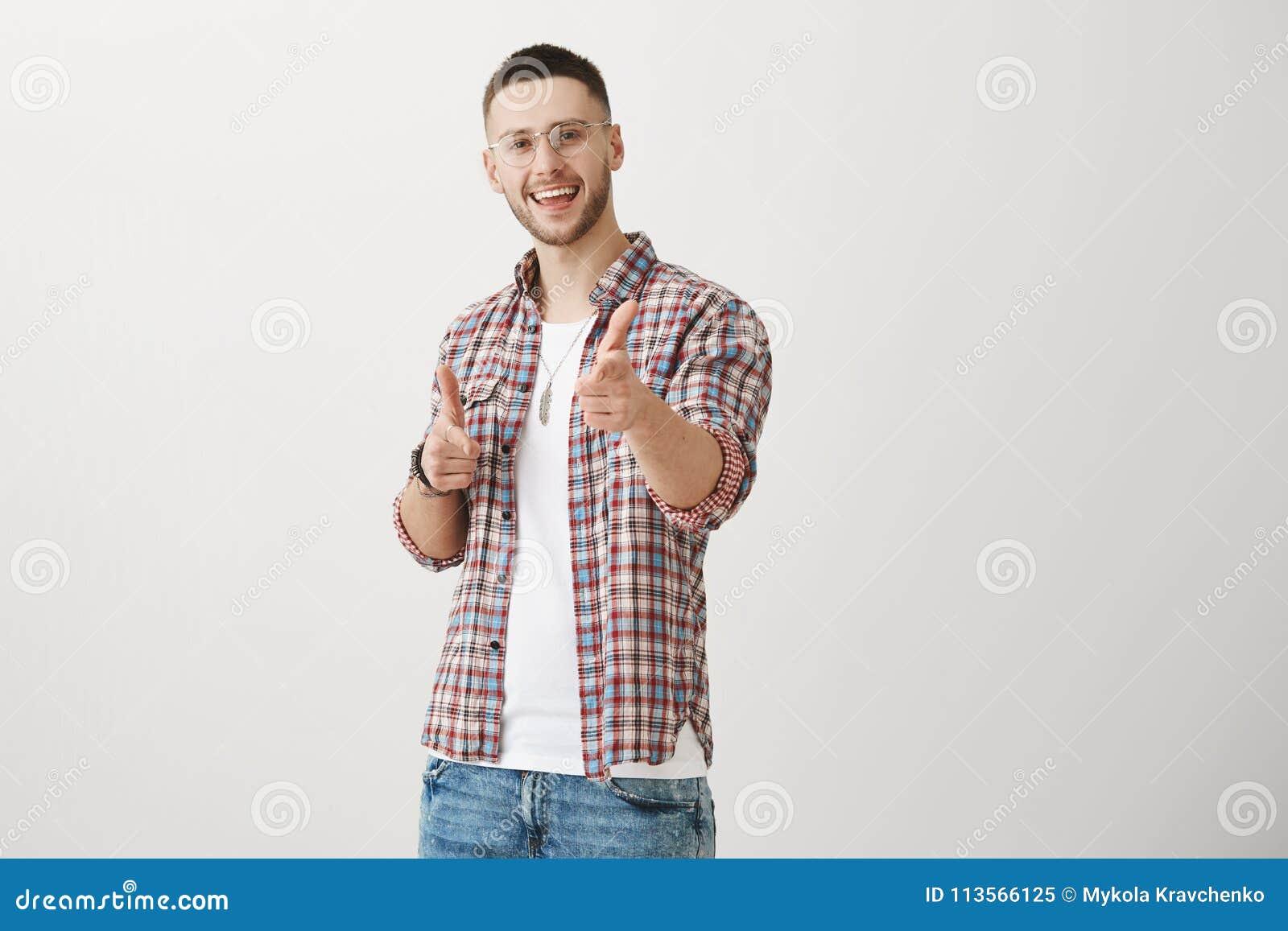 Вы уловили меня с вашим шармом Крытая съемка положительного привлекательного молодого человека с щетинкой, указывая на камеру с и