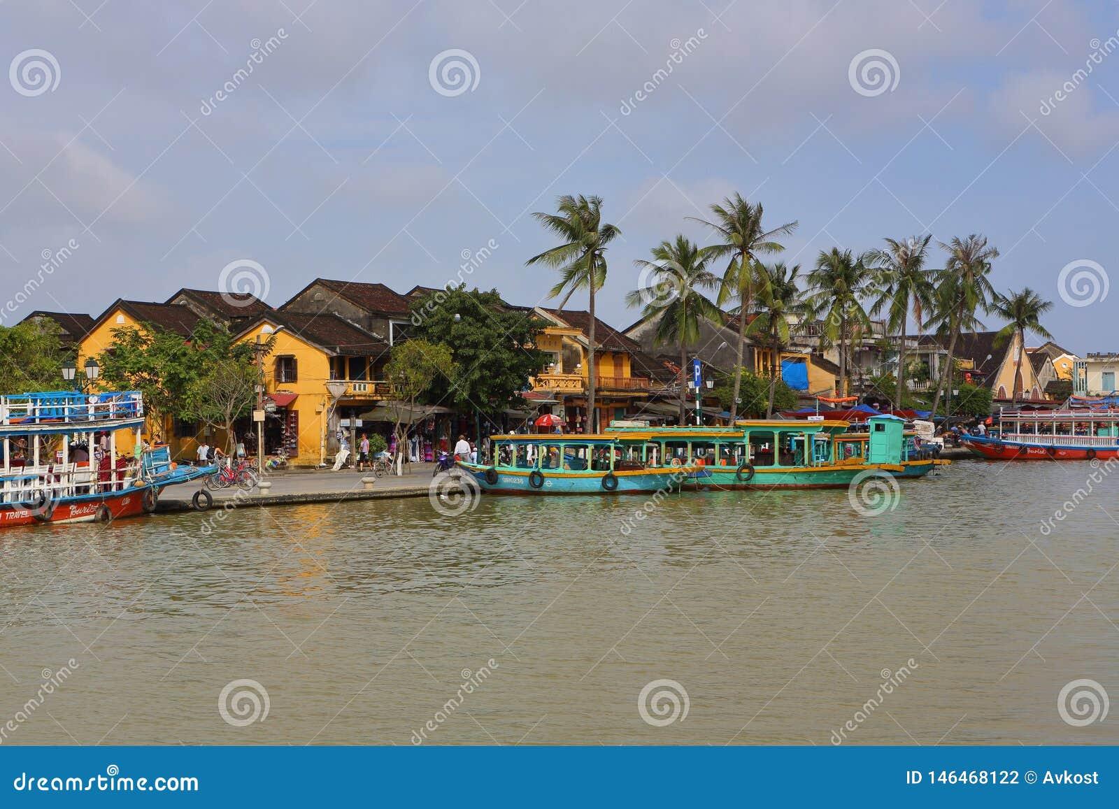 Вьетнам, Hoi - январь 2017: Поплавки шлюпки на реке Bon против фона домов на портовом районе в городке Hoi