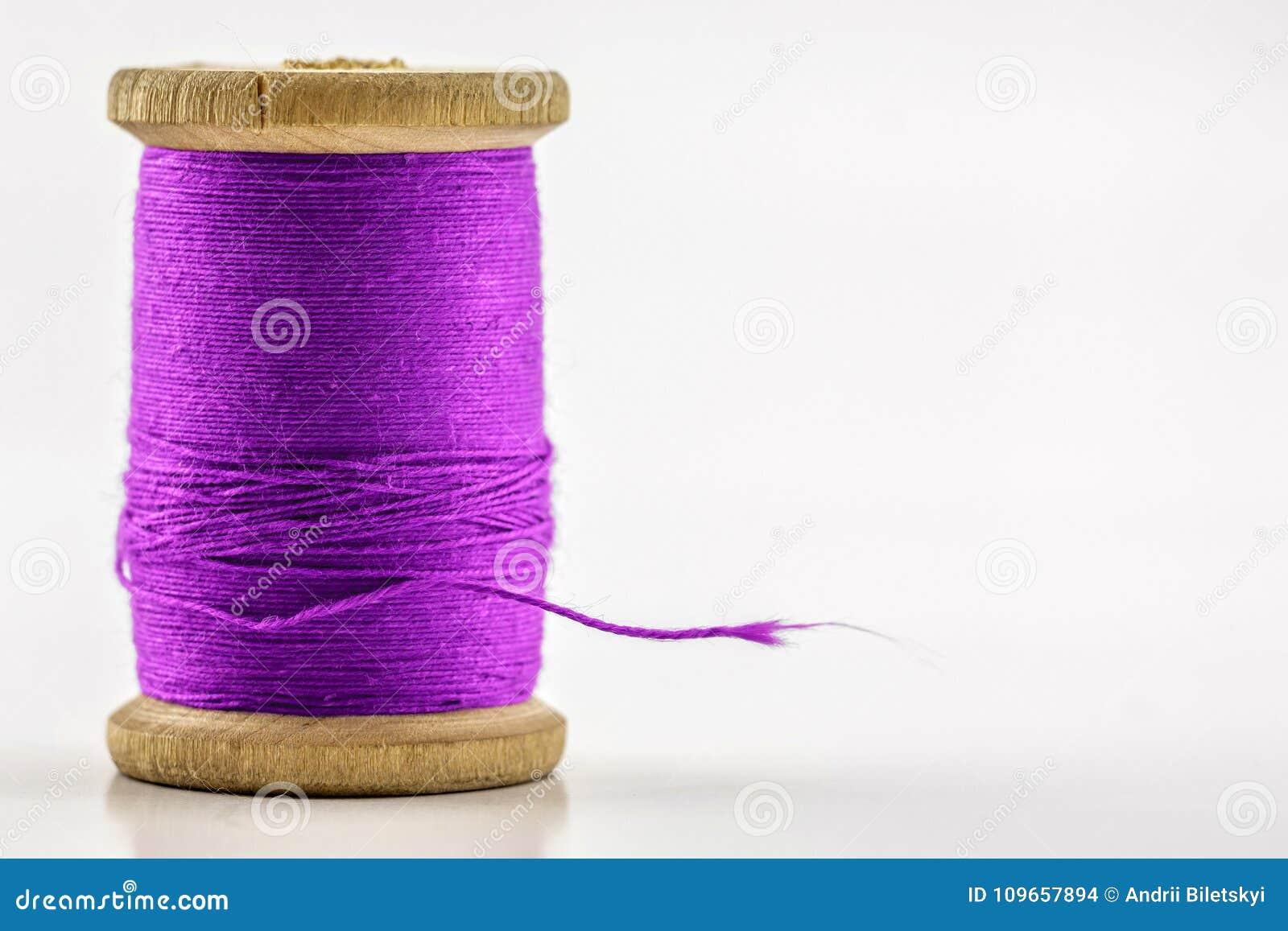 Вьюрок или катышка фиолетового шить потока на белизне отмело