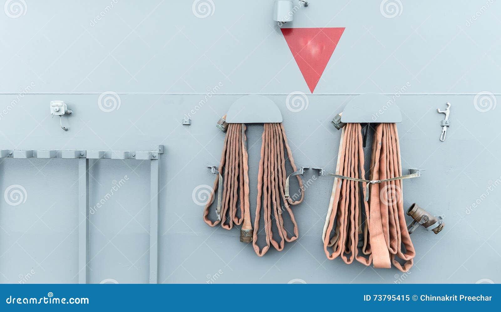Вьюрок пожарного рукава, установленный на серой предпосылке стены