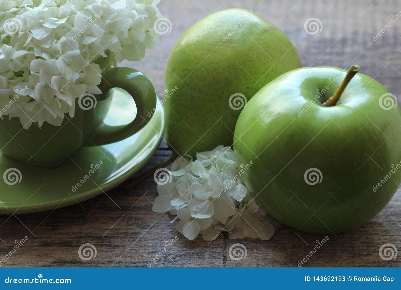 В зеленой чашке великолепное цветорасположение белых цветков, и рядом с зеленой грушей с яблоком