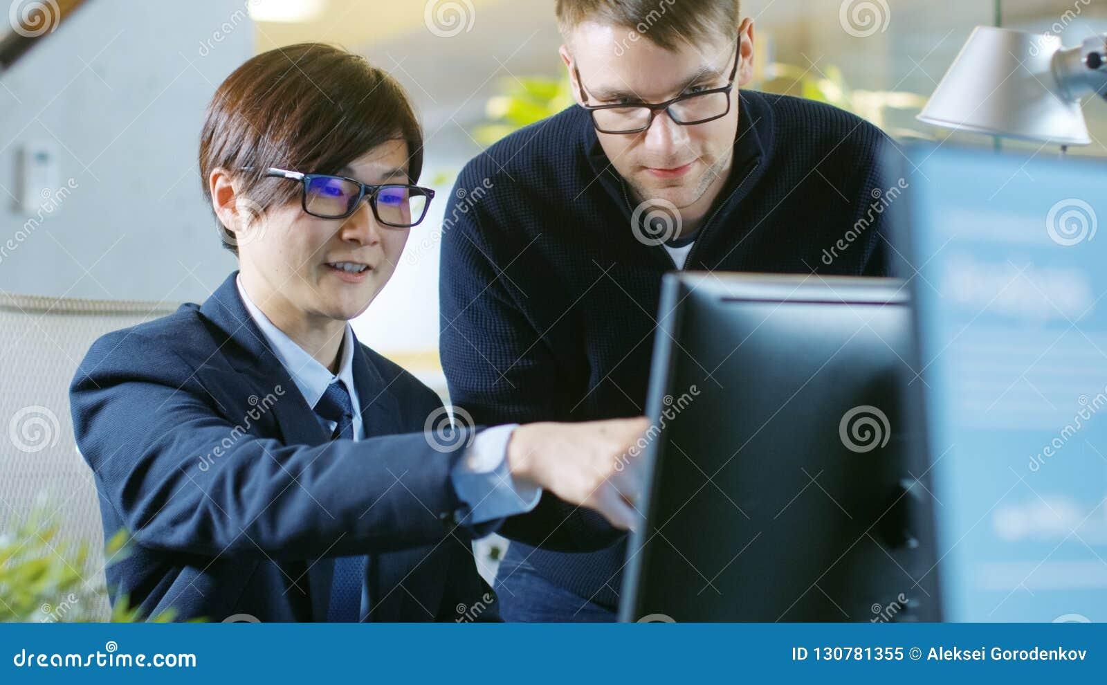 В офисе бизнесмен сидит на его разговаривать стола с его Collea