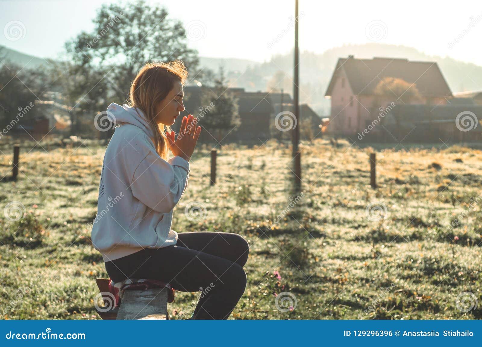 В утре девушка закрыла ее глаза, моля outdoors, руки сложенные в концепции молитве для веры, духовности, концепции вероисповедани