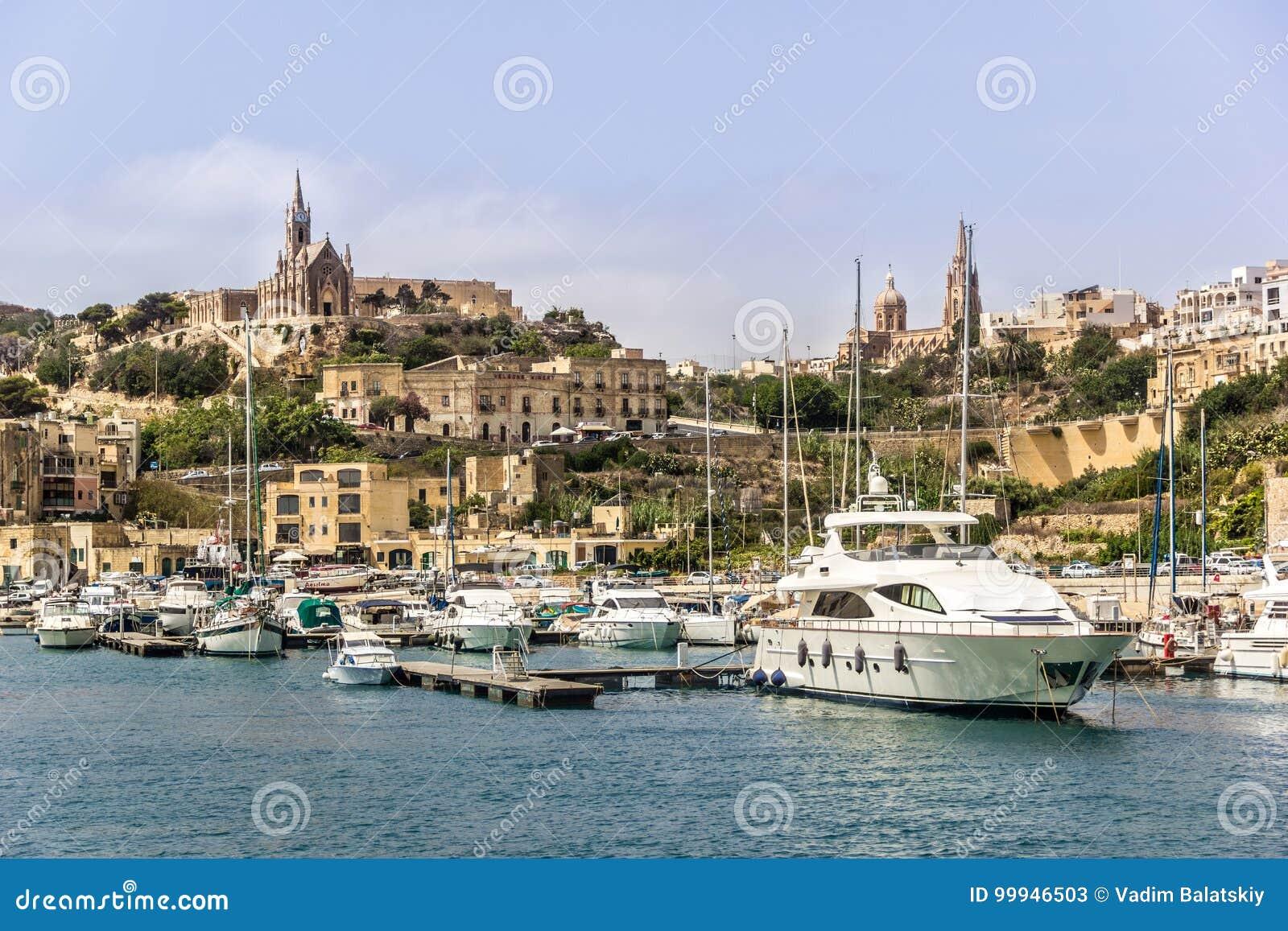 Гавань ` s Мальты с старыми висками архитектуры и различными шлюпками