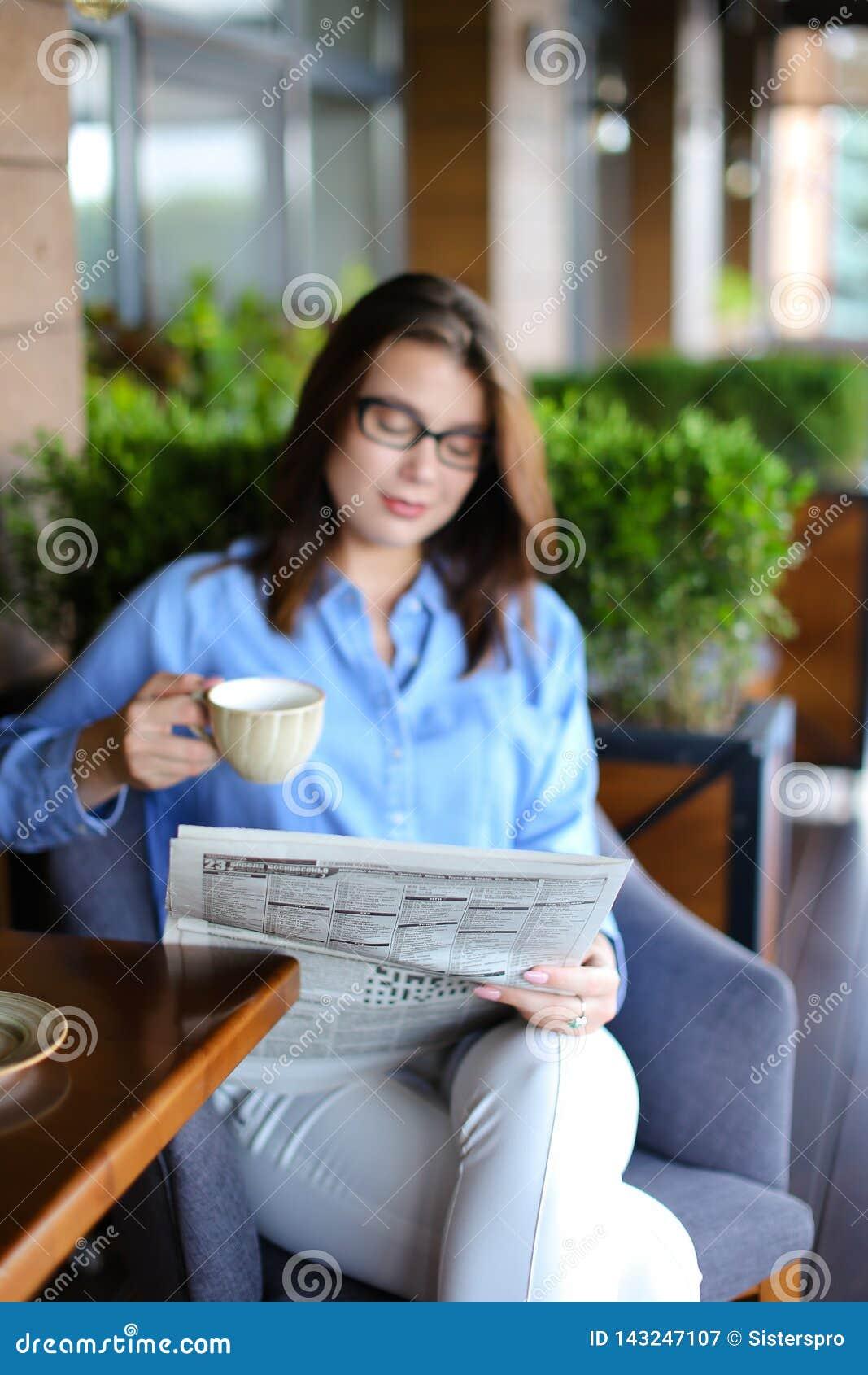 Газета чтения молодой женщины и smartphone использования на ресторане