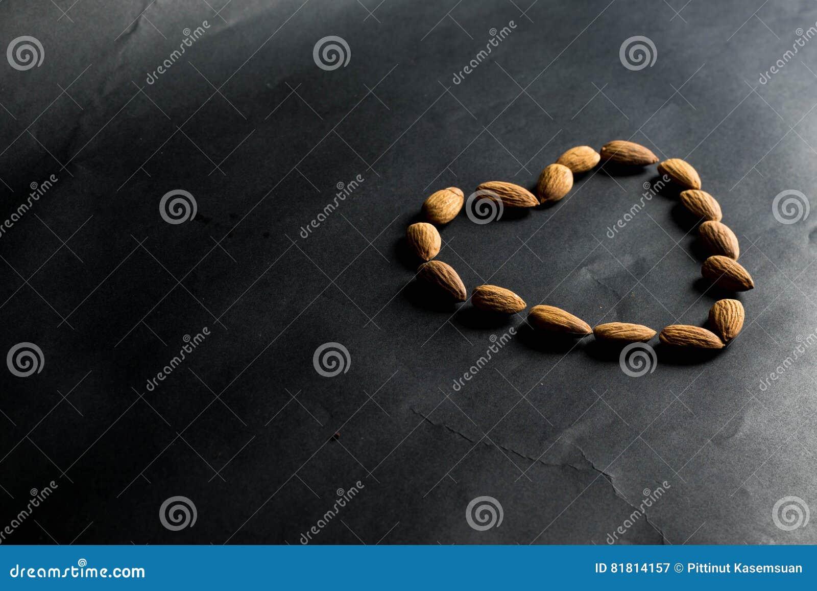 Гайки миндалины формируя сердц-форму на черной предпосылке