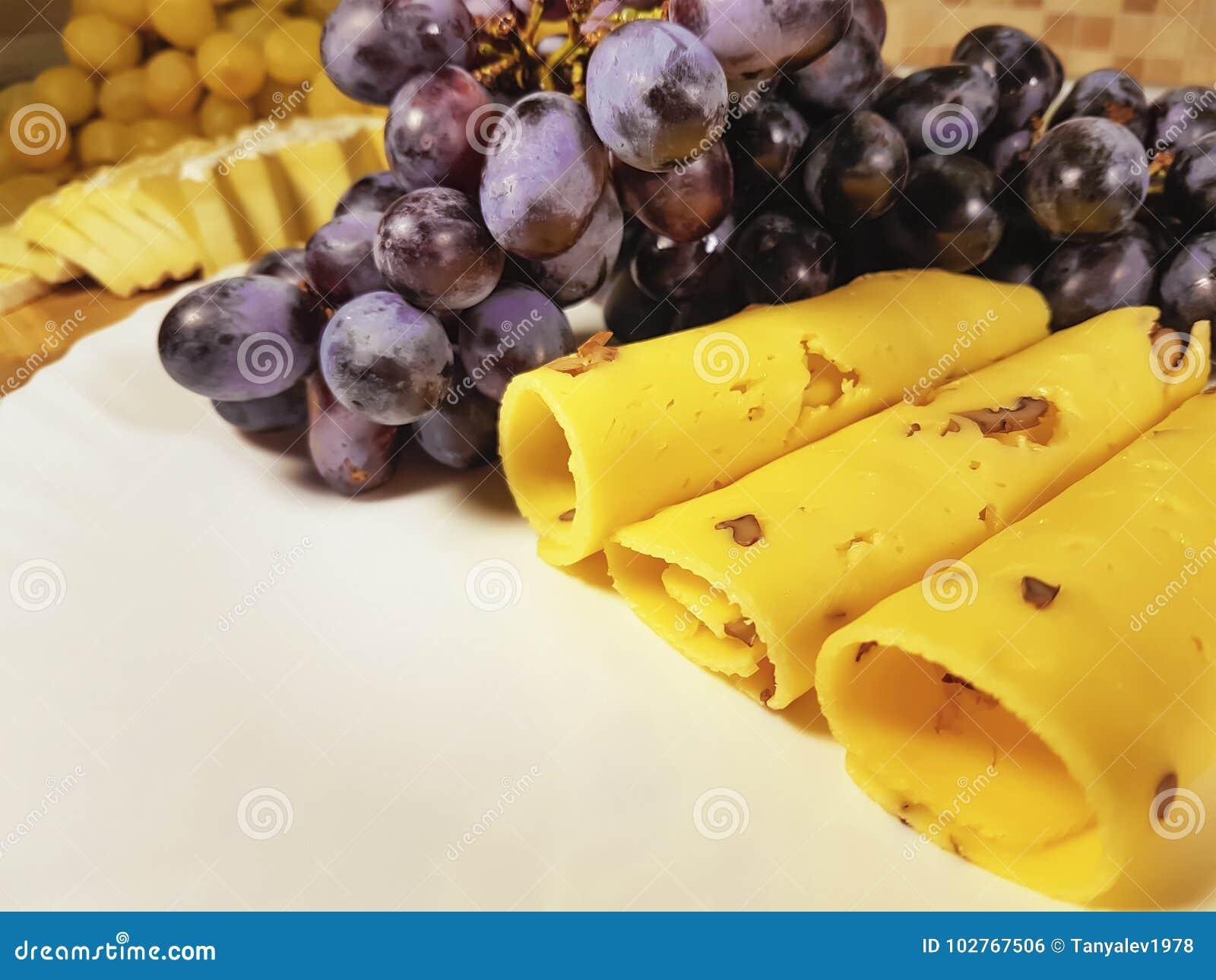 Гайки плиты натюрморта виноградин сыра