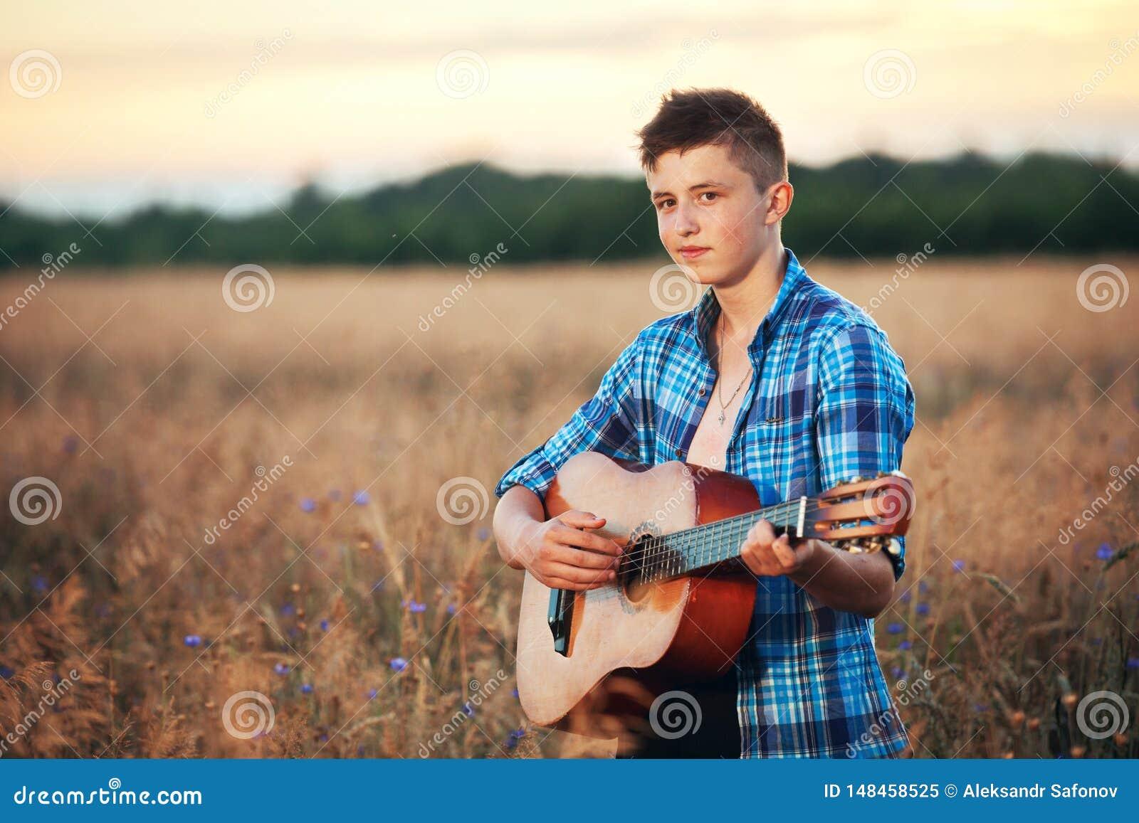 Гай с гитарой играя песни на природе захода солнца