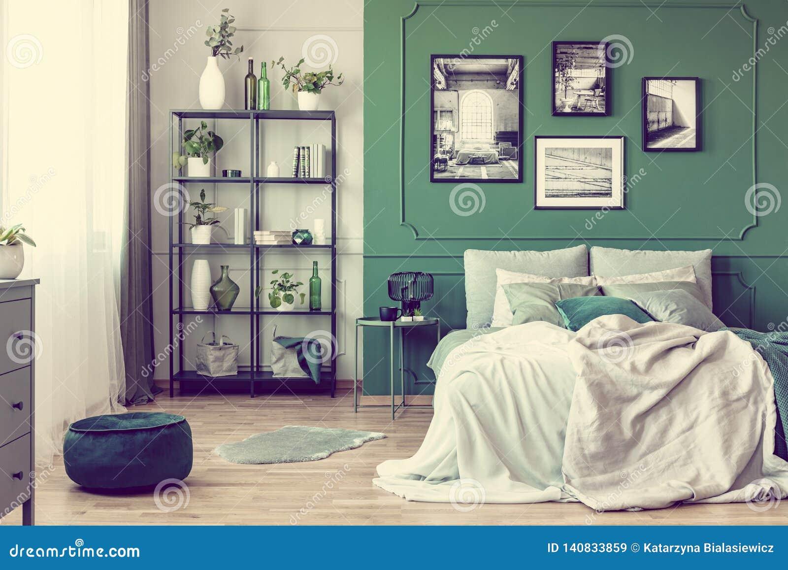 Галерея черно-белого плаката на зеленой стене за королевской кроватью с подушками и одеялом