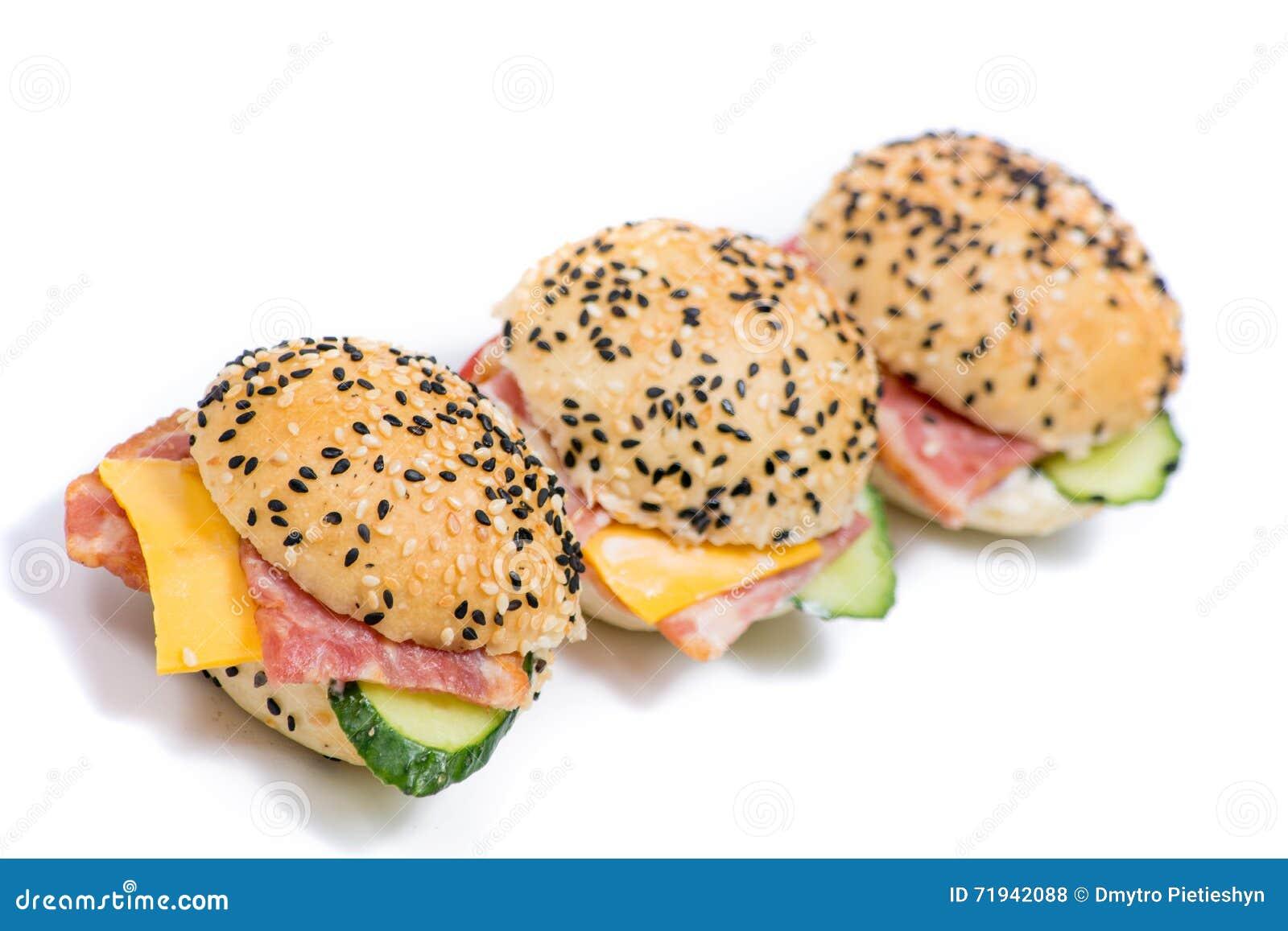 Гамбургеры с овощами и беконом на белой предпосылке