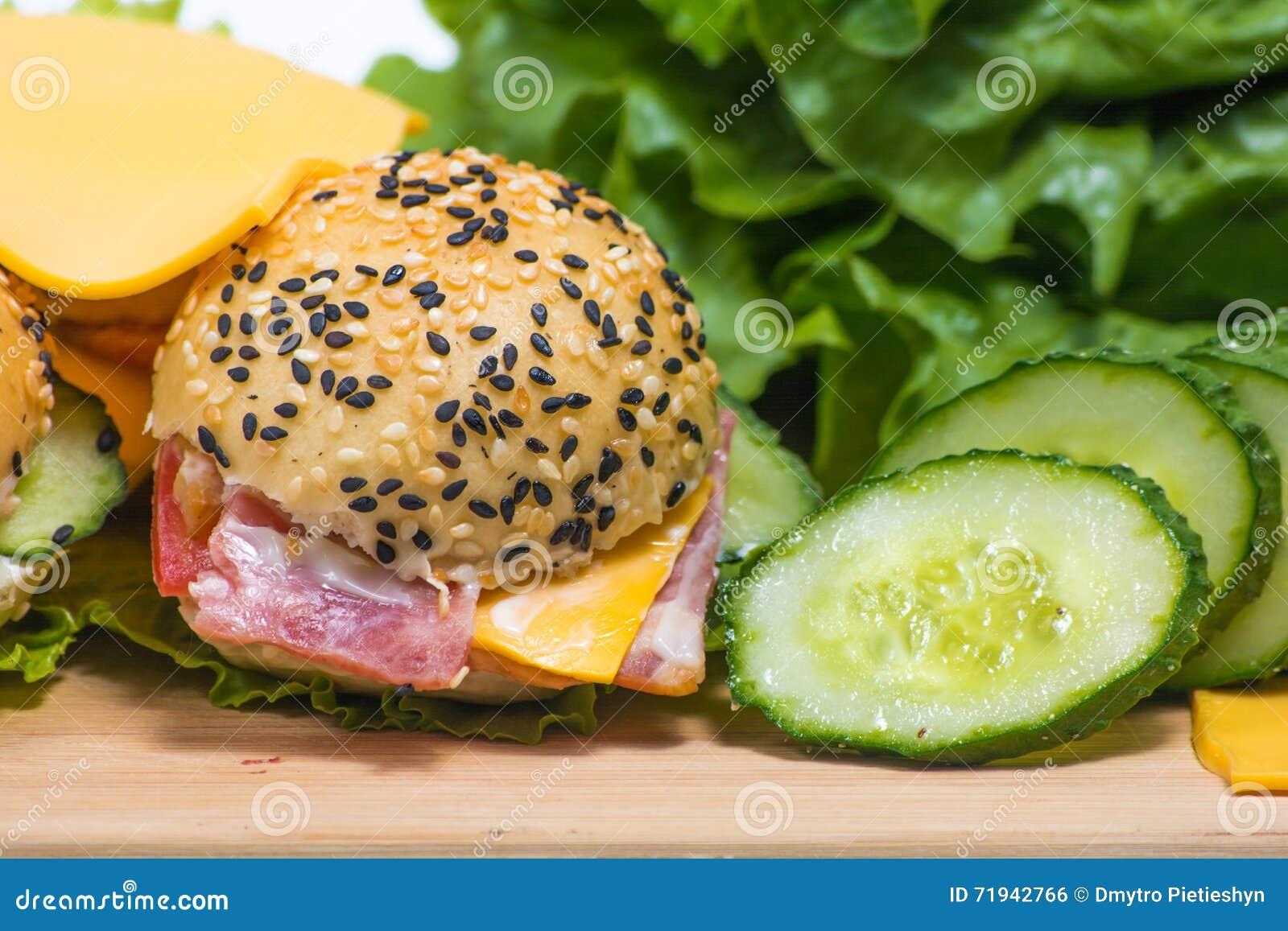 Гамбургеры с овощами и беконом на деревянном столе
