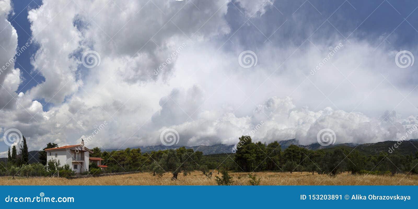 Гигантские облака кумулюса перед причаливая штормом лета в деревне на греческом острове Evia