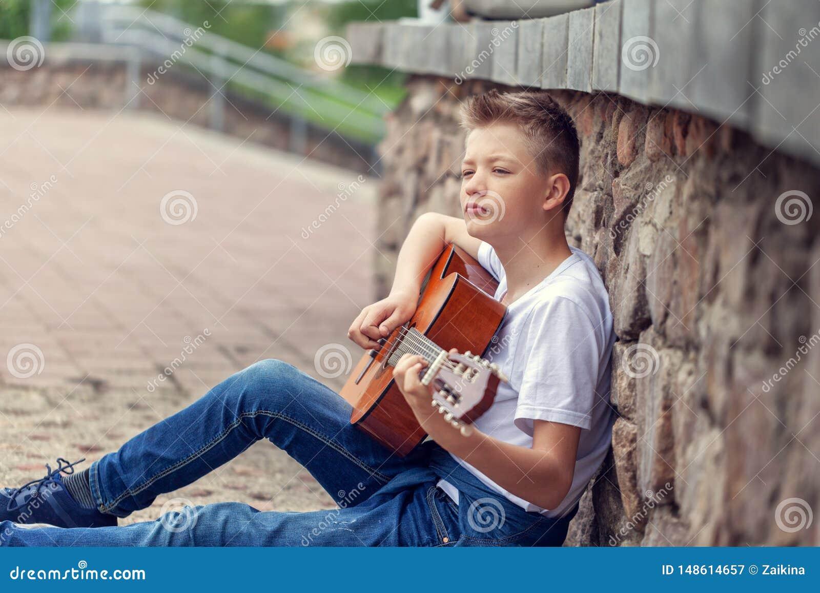 Гитара подростка акустическая играя усаживание на шагах в парк