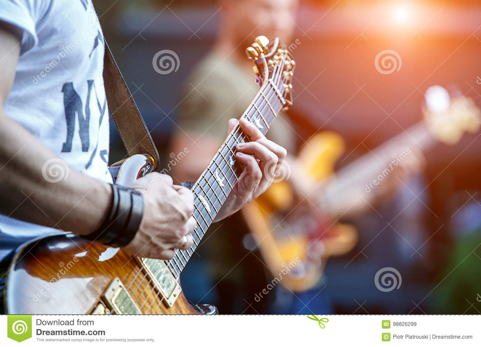 Гитарист играя концерт в реальном маштабе времени с рок-группой