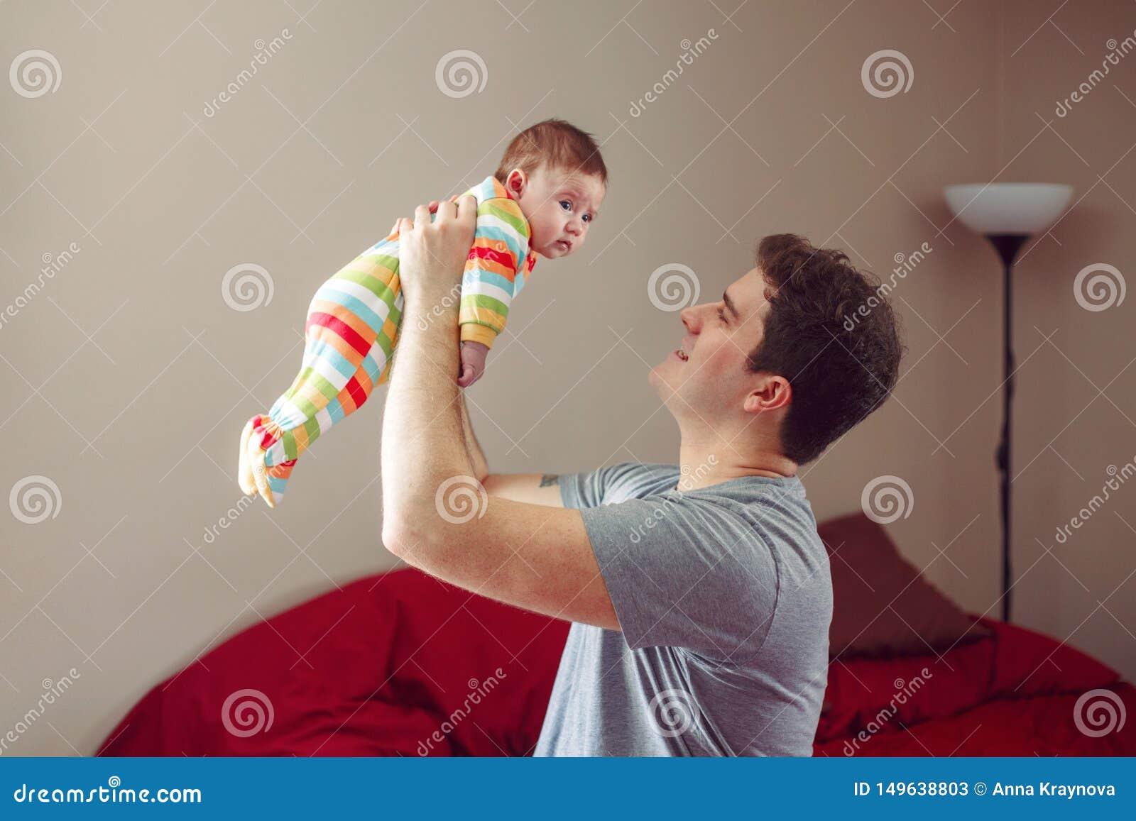 Говорить кавказского отца обнимая и усмехаясь с newborn младенцем Мужской ребенок удерживания родителя человека