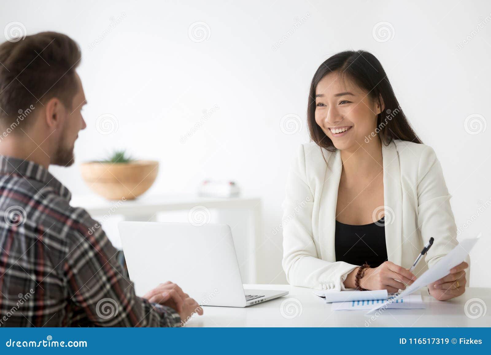 Говорить hr дружелюбного азиата усмехаясь к выбранному на собеседовании для приема на работу