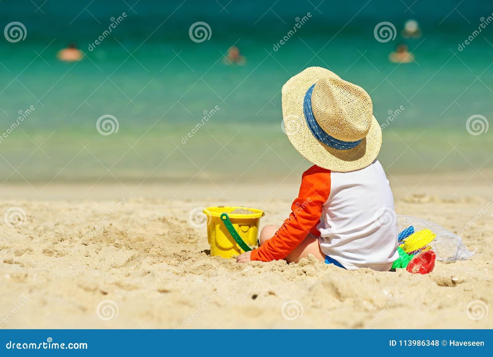 Годовалый малыш 2 играя на пляже