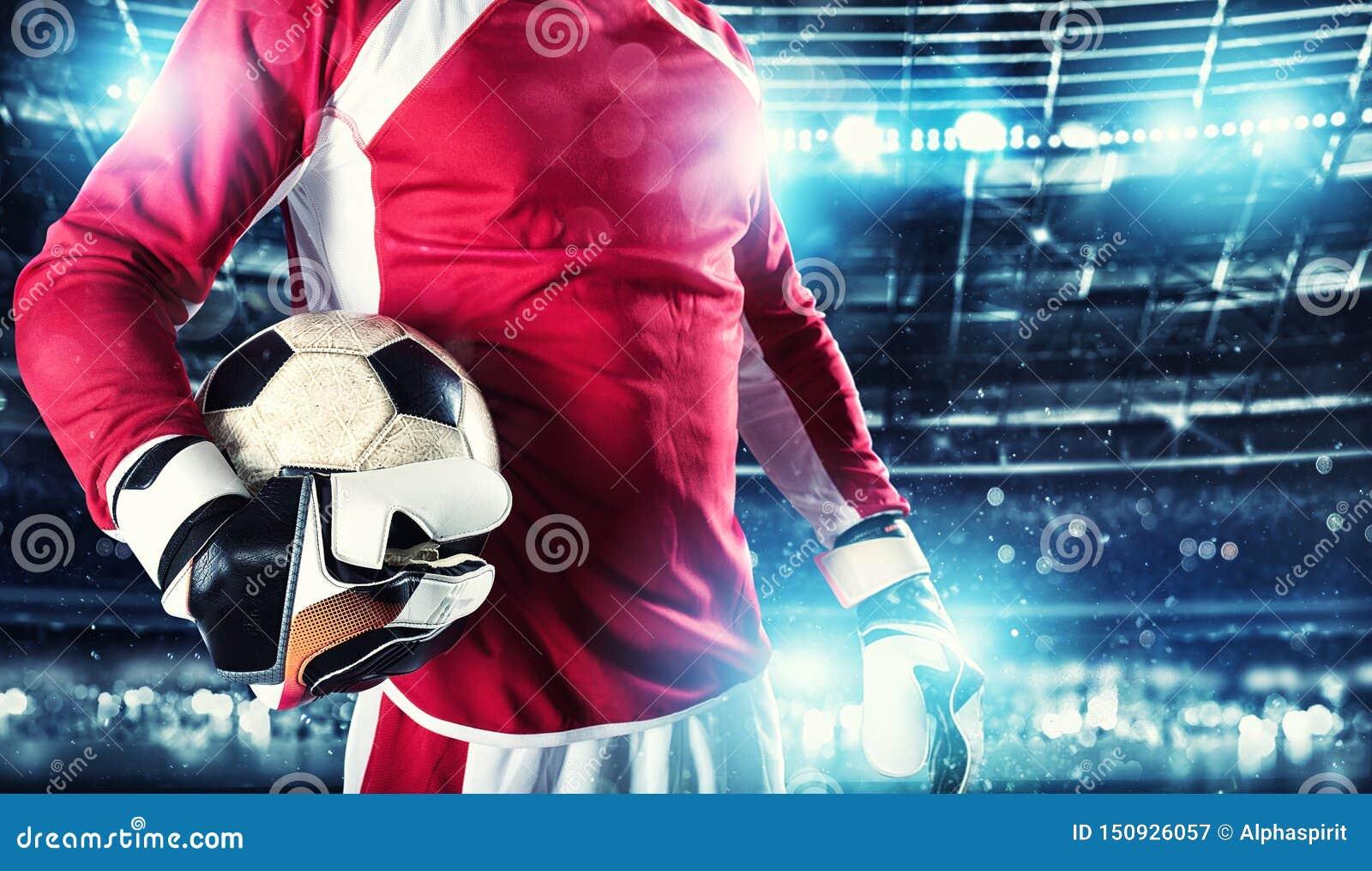 Голкипер держит шарик в стадионе во время футбольного матча
