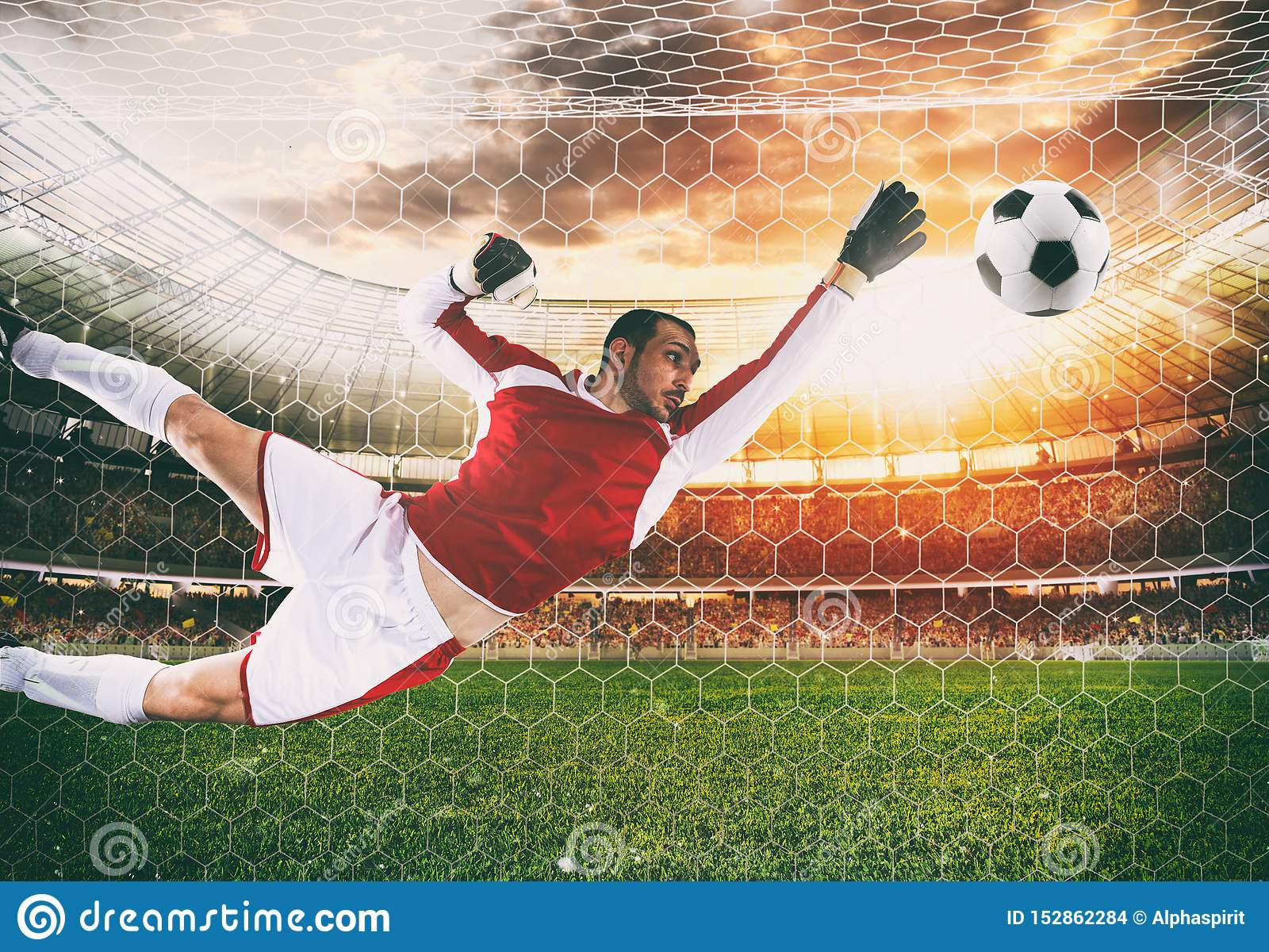 Голкипер улавливает шарик в стадионе во время футбольного матча