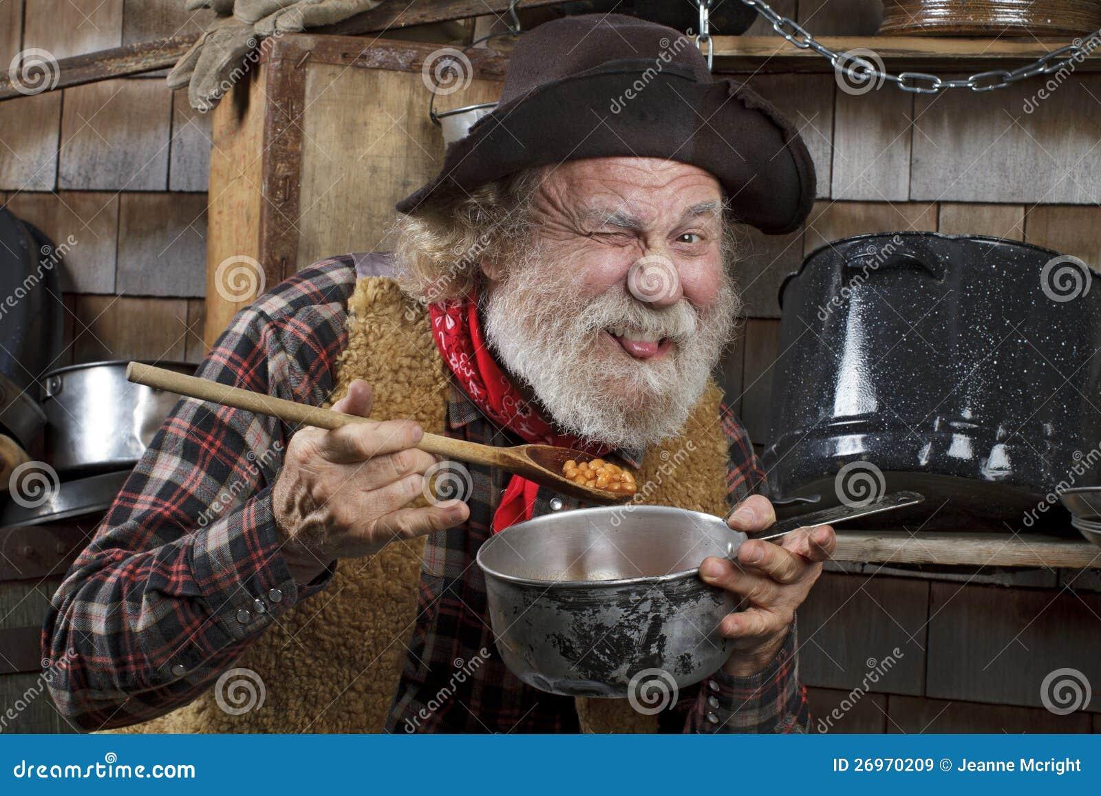Голодный старый ковбой есть фасоли от кастрюльки