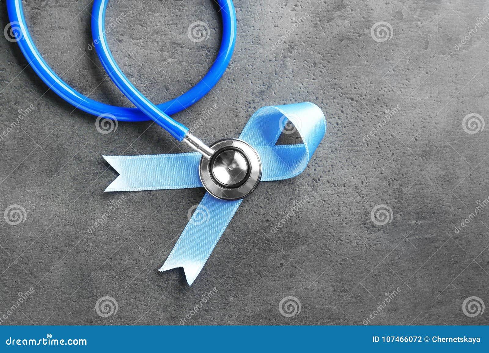 Голубая лента и стетоскоп на серой предпосылке