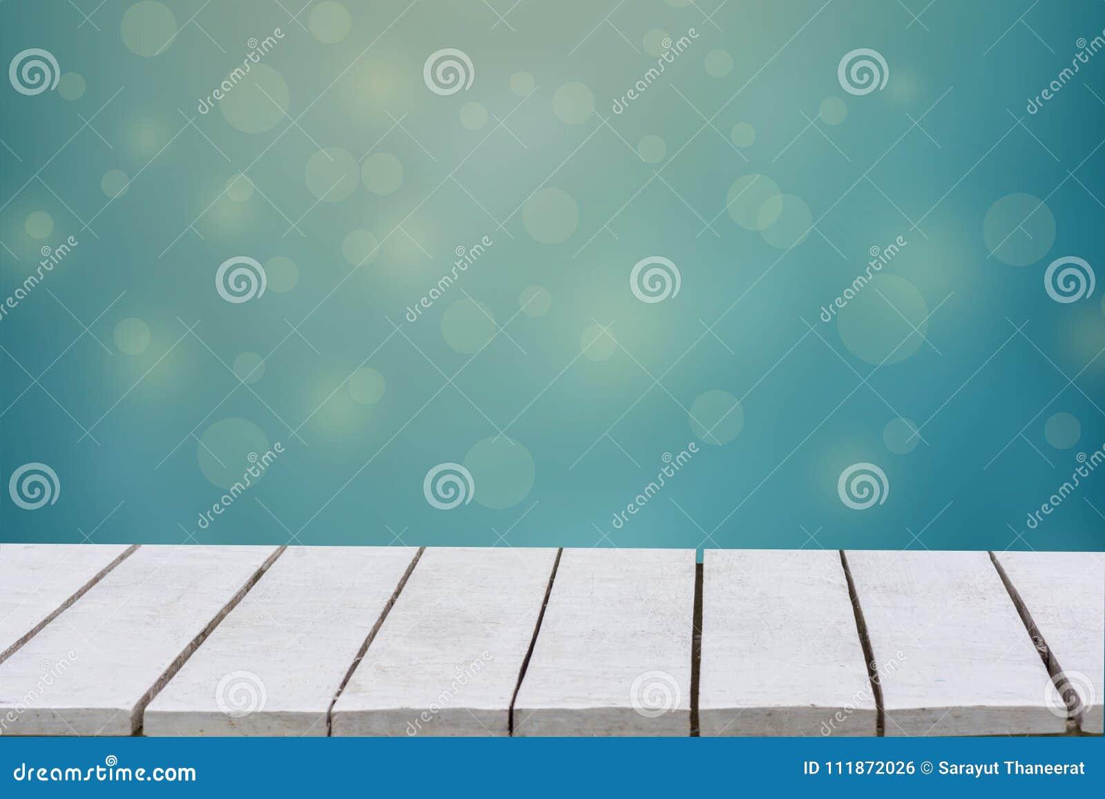 Голубая предпосылка с селективным фокусом Зеленая предпосылка имеет лист и траву bokeh на белом деревянном поле Пустая таблица пу