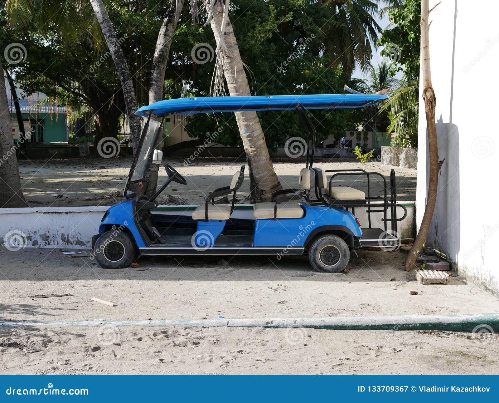 Голубая тележка гольфа на песчаном пляже в Мальдивах