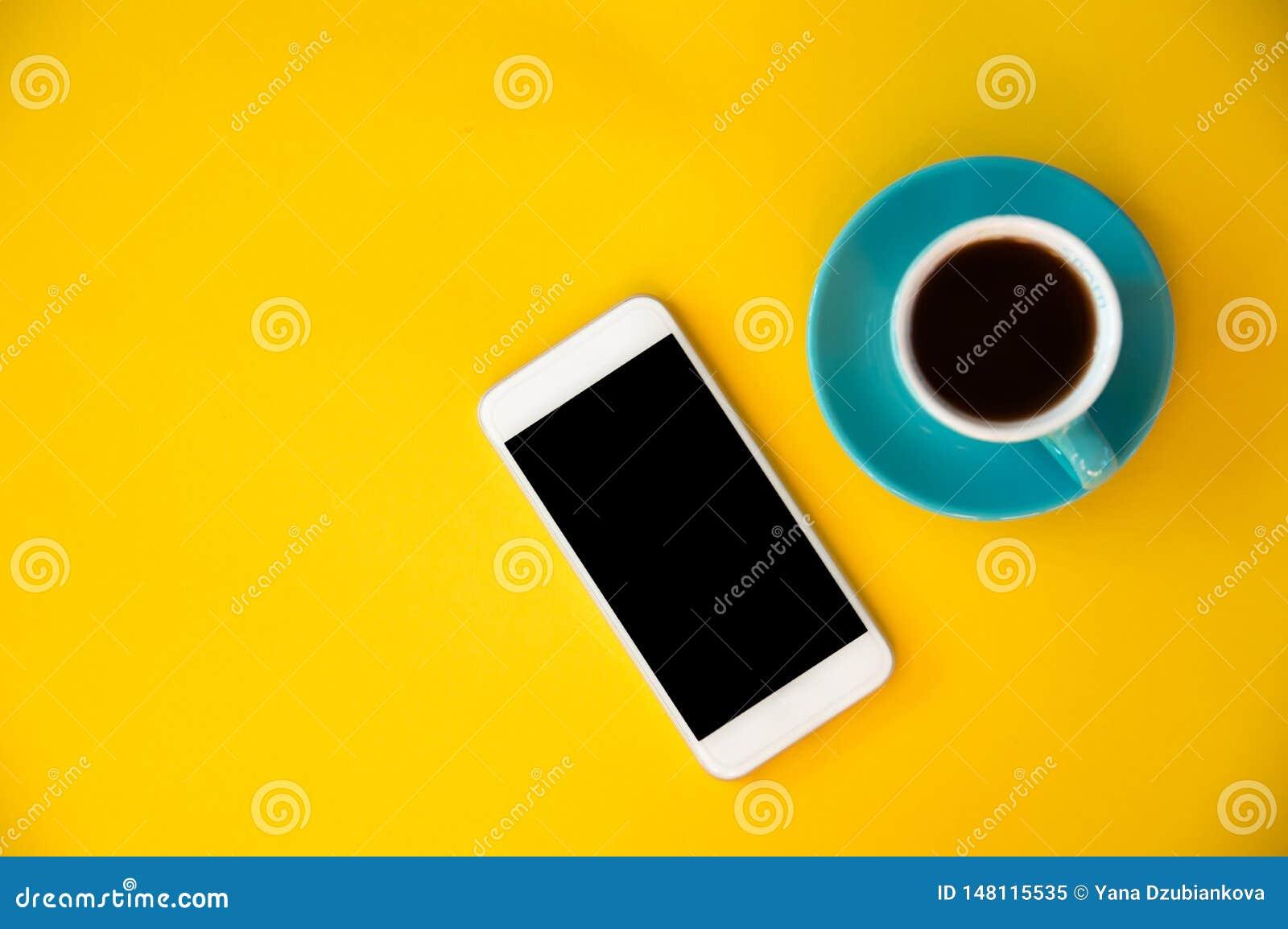 Голубая чашка с кофе и мобильным телефоном стоит на пинке и голубой предпосылке Завтрак утра, дело