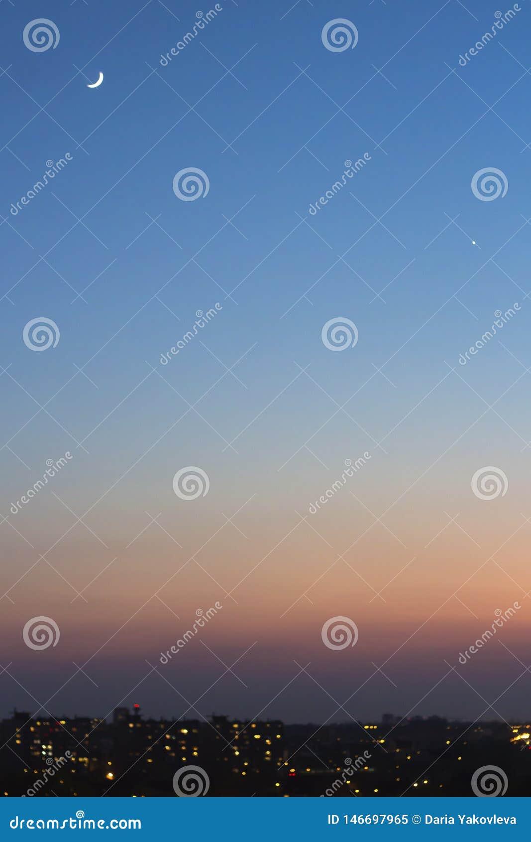 Голубое небо захода солнца с полумесяцем
