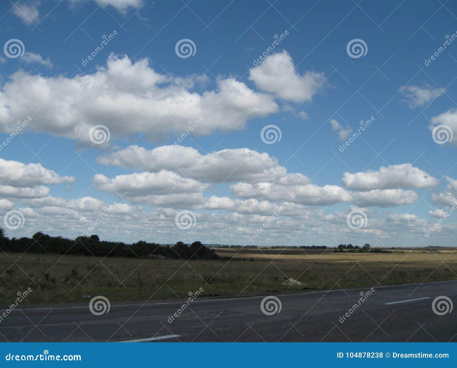 Голубое небо и облака над полем
