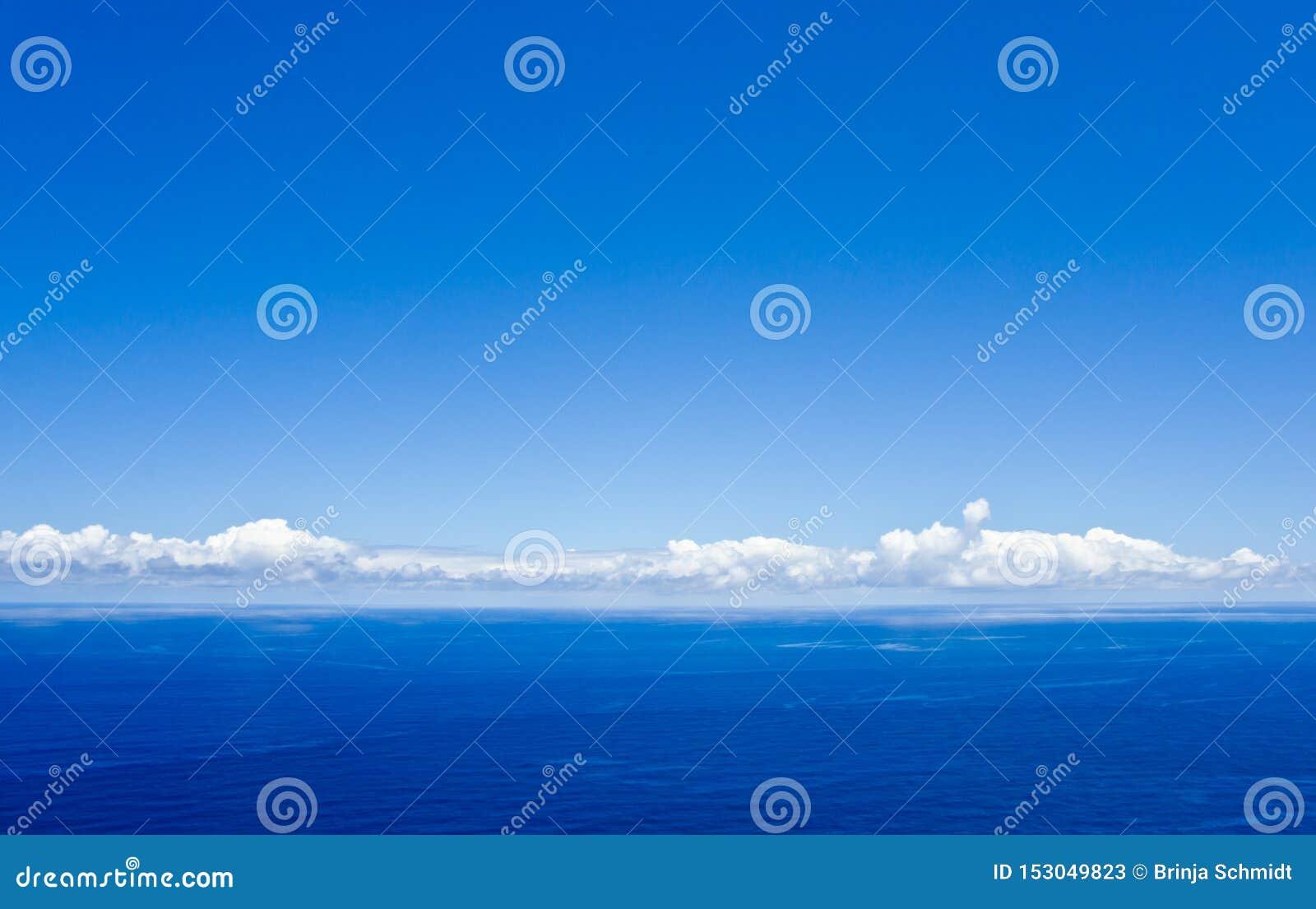 Голубое небо с некоторыми белыми облаками над Атлантическим океаном